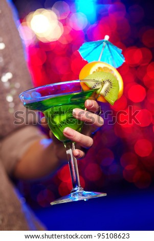 Young woman in a sparkling dress holding a cocktail at a birthday party