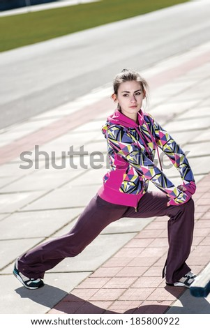 Young Woman in a sports suit does warm up and stretching on the street the stadium in the afternoon. - stock photo
