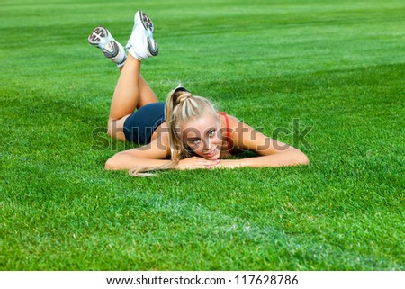 Young woman in a sports suit lying on a green soccer field at the stadium - stock photo