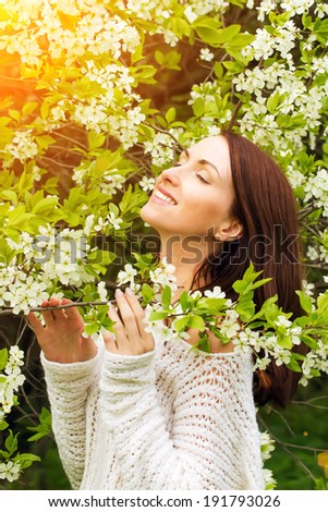 Young woman in a spring park against blossom flowers background  - stock photo