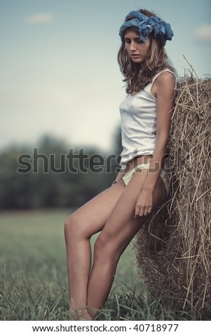 Young woman in a summer field. Calm pensive mood. - stock photo