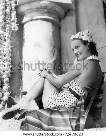 Young woman in a sun suit sitting on a chair - stock photo