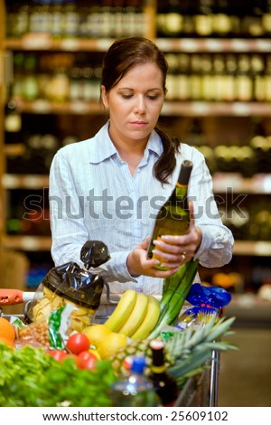 Young woman in a supermarket to buy wine - stock photo