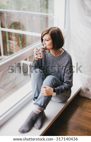Young woman in a sweater and boyfriend jeans relaxing near big window with mountains view - stock photo