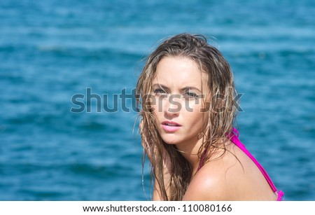 Young woman in a swimsuit at the beach. - stock photo