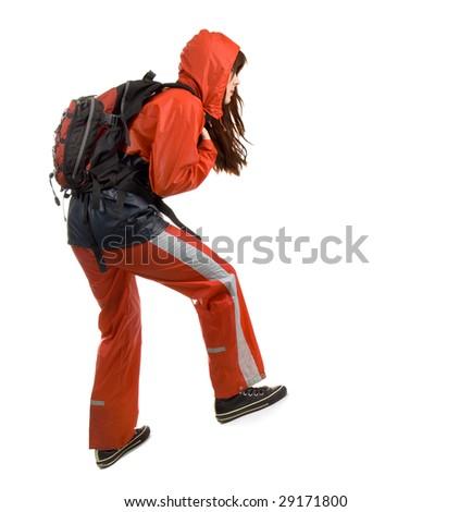 Young woman in a waterproof suit walking upwards - stock photo