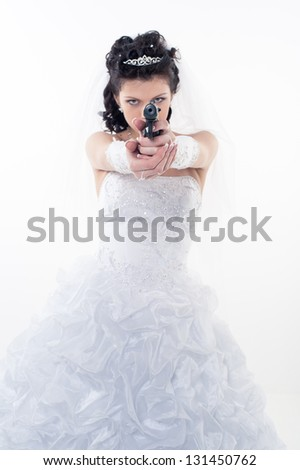 Young woman in a wedding dress with gun on a white background.A bride holding a gun pointing it at the camera. wedding. studio. - stock photo