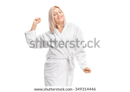 Young woman in a white bathrobe stretching herself isolated on white background - stock photo