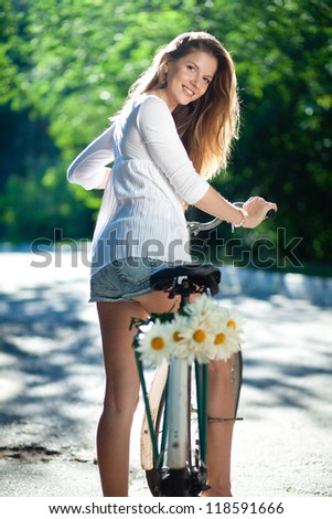 Young woman in a white blouse and denim shorts clinging to an old bicycle handlebars. Back view - stock photo