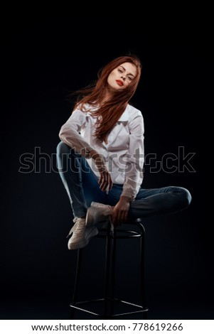 young woman in a white shirt sits on a chair on a black background, studio, sexy