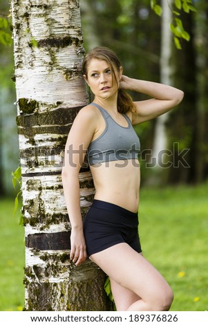 Young woman in a workout outfit posing outdoors - stock photo