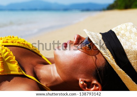 Young woman in a yellow swimsuit, a hat and sunglasses laying down on a sandy beach of Thailand on a sunny summer day - stock photo