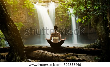 Young woman in a yoga pose sit at the waterfall, she felt relaxed. The exercise - stock photo