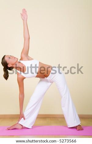 Young woman in a yoga position (Utthita Trikonasana) - stock photo