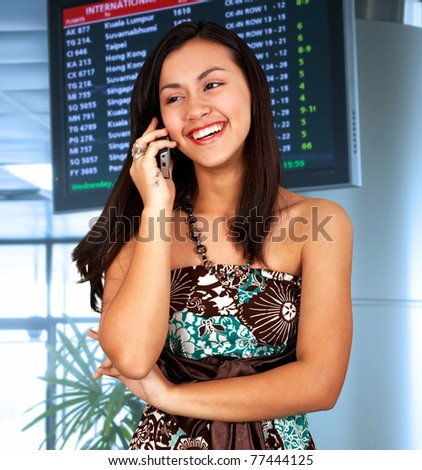 Young woman in an airport talking on the phone - stock photo