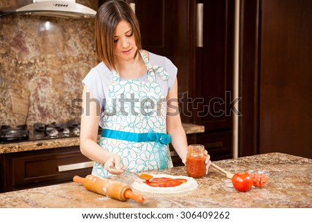 Young woman in an apron adding some tomato sauce to her homemade pizza - stock photo