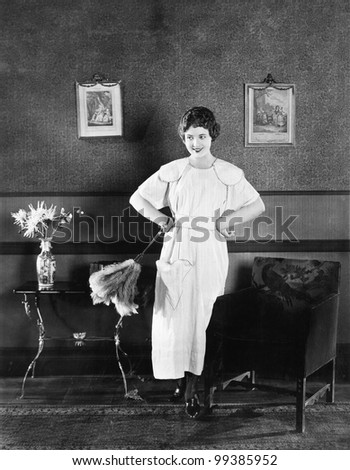 Young woman in an apron and a duster standing in a living room - stock photo