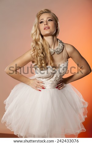 young woman in an elegant white dress posing in studio