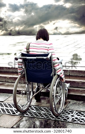 young woman in an invalid carriage - stock photo