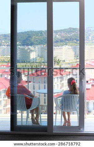 Young woman in an orange dress and daughter sitting on the terrace in the room, view through glass - stock photo