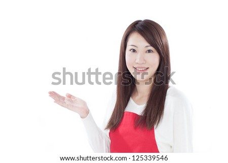 Young woman in apron showing copy space, isolated on white background - stock photo