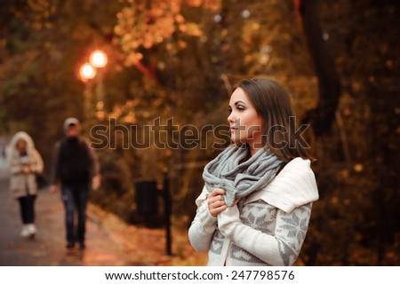 Young woman in autumn evening park against passers backdrop. - stock photo