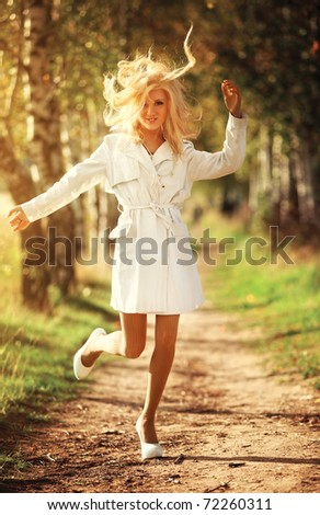 Young woman in autumn park fun. Film style colors. - stock photo