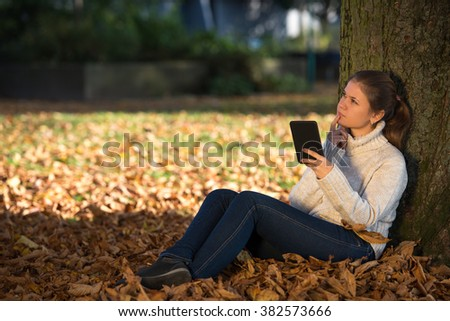 young woman in autumn park sitting near tree reading ebook