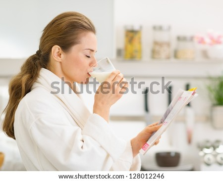 Young woman in bathrobe with magazine and drinking milk - stock photo