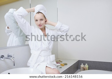 Young woman in bathroom, hands on head - stock photo