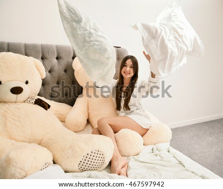 Young woman in bed throws pillows. Pajama party.