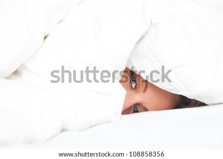 young woman in bed under white blanket - stock photo
