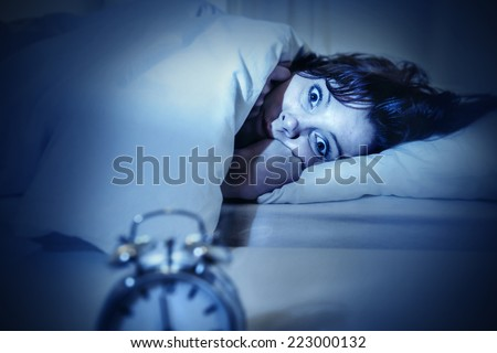 young woman in bed with alarm clock and eyes opened suffering insomnia and sleep disorder thinking about his problem on dark studio lighting in sleeping and nightmare issues - stock photo