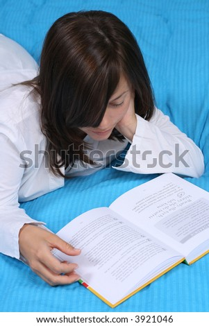 young woman in bedroom - relax with book - stock photo