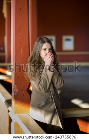 Young woman in beige coat warming her breath - stock photo