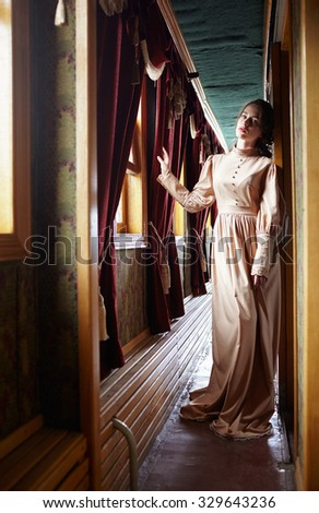 Young woman in beige vintage dress of early 20th century standing near window in corridor of retro railway train