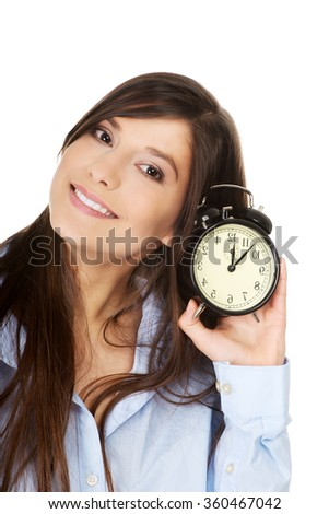 Young woman in big shirt holding alarm clock. - stock photo