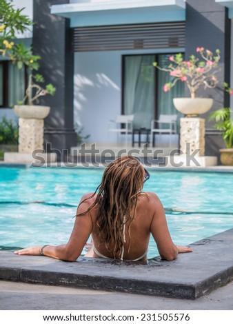 Young woman in bikini at the swimming pool in Bali Indonesia - stock photo
