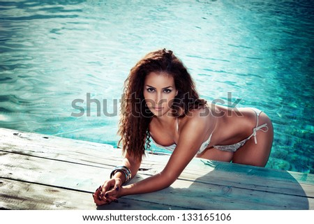 young woman in bikini in the pool outdoor shot summer day - stock photo