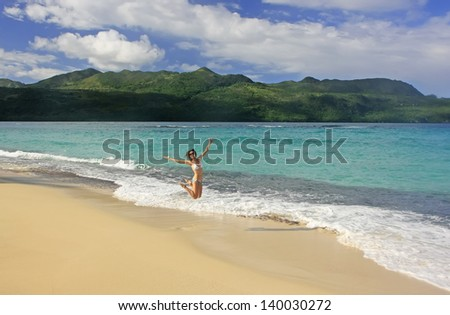 Young woman in bikini jumping at Rincon beach, Samana peninsula, Dominican Republic