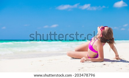 young woman in bikini lying on white sand beach
