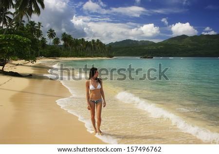 Young woman in bikini walking at Rincon beach, Samana peninsula, Dominican Republic - stock photo