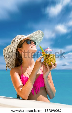 Young woman in bikini wearing a straw hat and enjoying a fresh pineapple cocktail by the swimming pool - stock photo