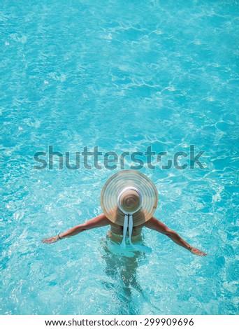 Young woman in bikini wearing a straw hat at the swimming pool - stock photo
