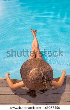 Young woman in bikini wearing a straw hat in the swimming pool - stock photo