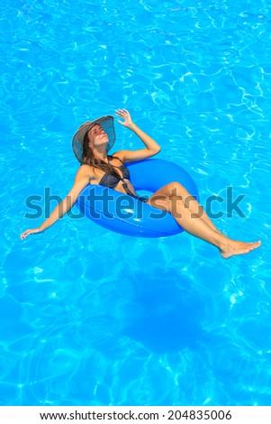 Young woman in bikini wearing a straw hat in the swimming pool - stock photo