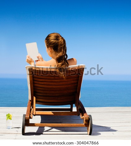Young woman in bikini with notepad at the beach