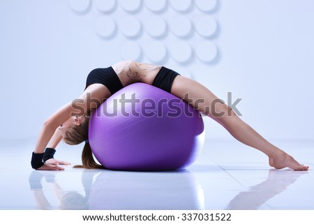 Young woman in black clothing stretching on fitness ball in modern white interior. Tattoo on body.
