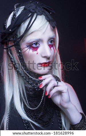 Young woman in black dress and with bloody tears. - stock photo