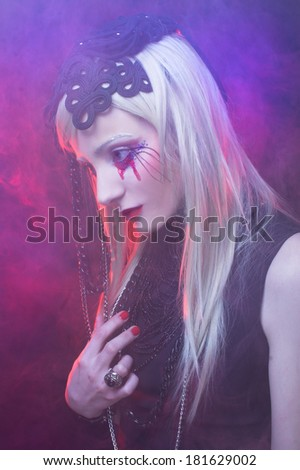 Young woman in black dress and with bloody tears.